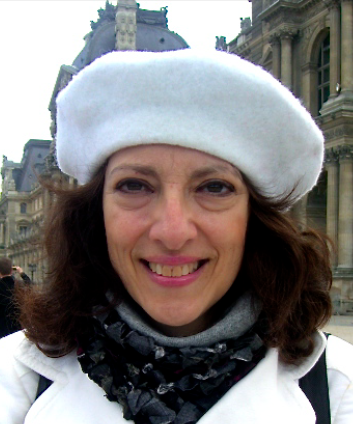 Scholar Alma Gotlieb in a white beret standing in front of buildings