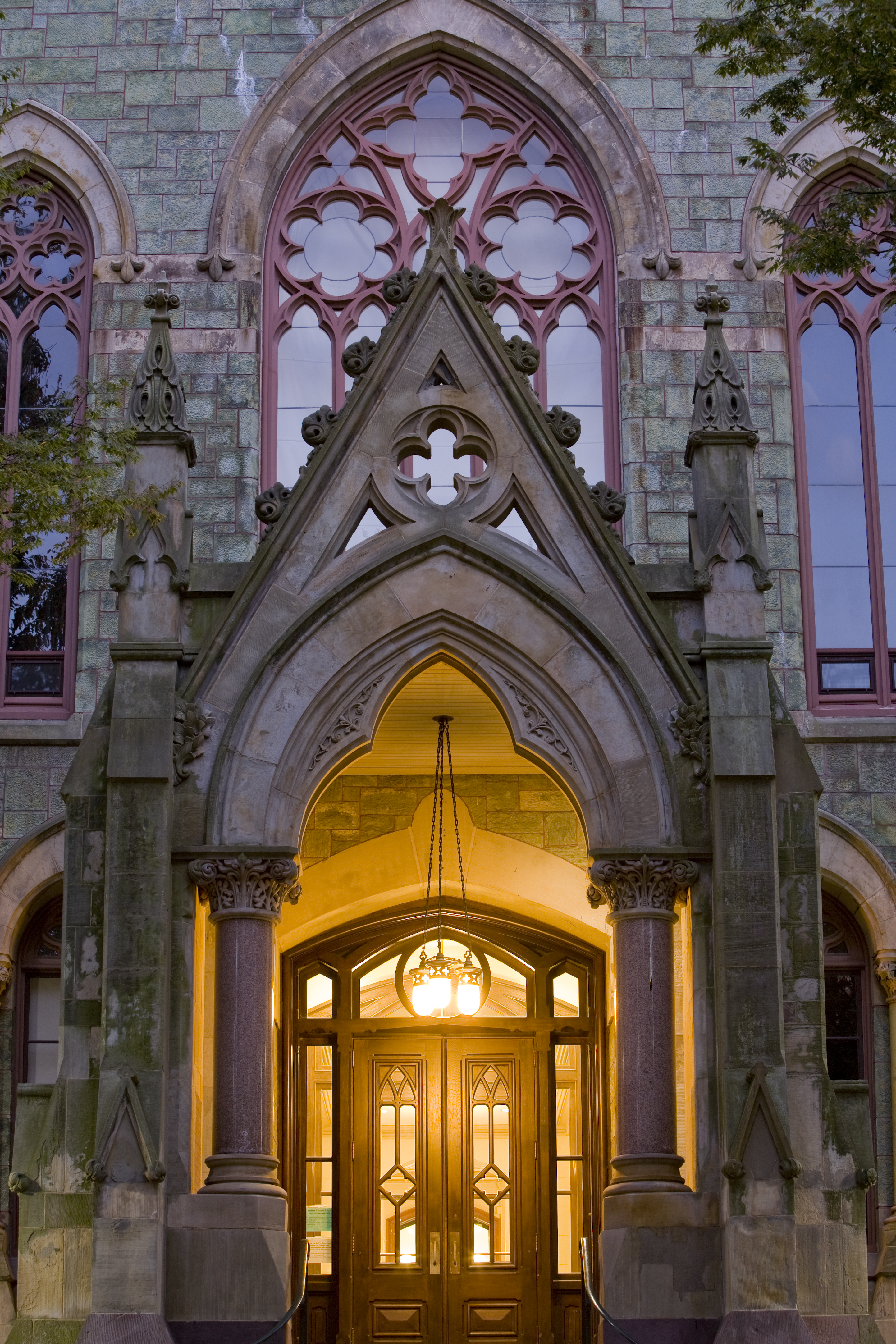 illuminated College Hall entry at dusk