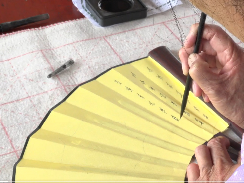 Film still from Her Words, woman writing calligraphy on a yellow hand fan