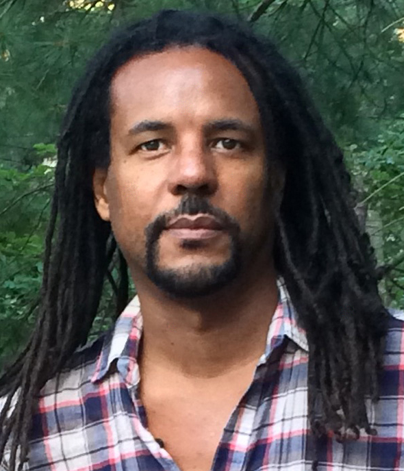 Headshot of author Colson Whitehead standing in front of trees