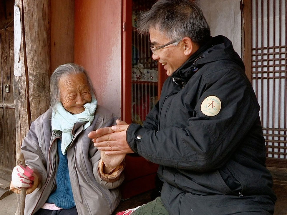 Film still from The Wandering Chef. A man sitting on the right next to an elderly woman to his left in Korea.