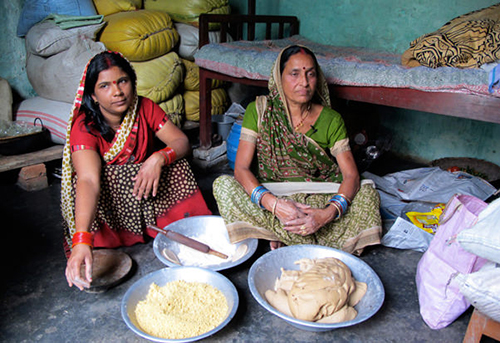 Film still from Dail Puri Diaspora two women in saris seated on the ground with baskets of legumes and grains