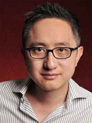 Filmmaker Hao Wu wearing a shirt with vertical stripes in front of a red background
