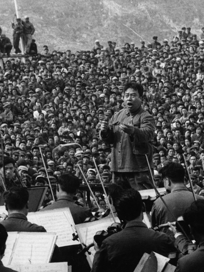 Li Delun conductor leading a band in front of a large crowd in black and white