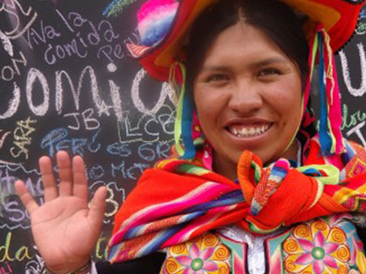 Film still from Sonia's Dream. Sonia Mamani, an Aymara chef standing in front of a chalkboard filled with phrases in Espanol.