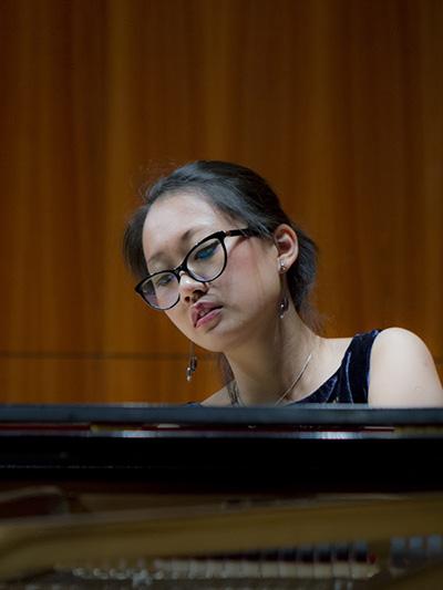 Ania Vu behind a piano