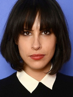 Desiree Akhavan in front of a Blue Background