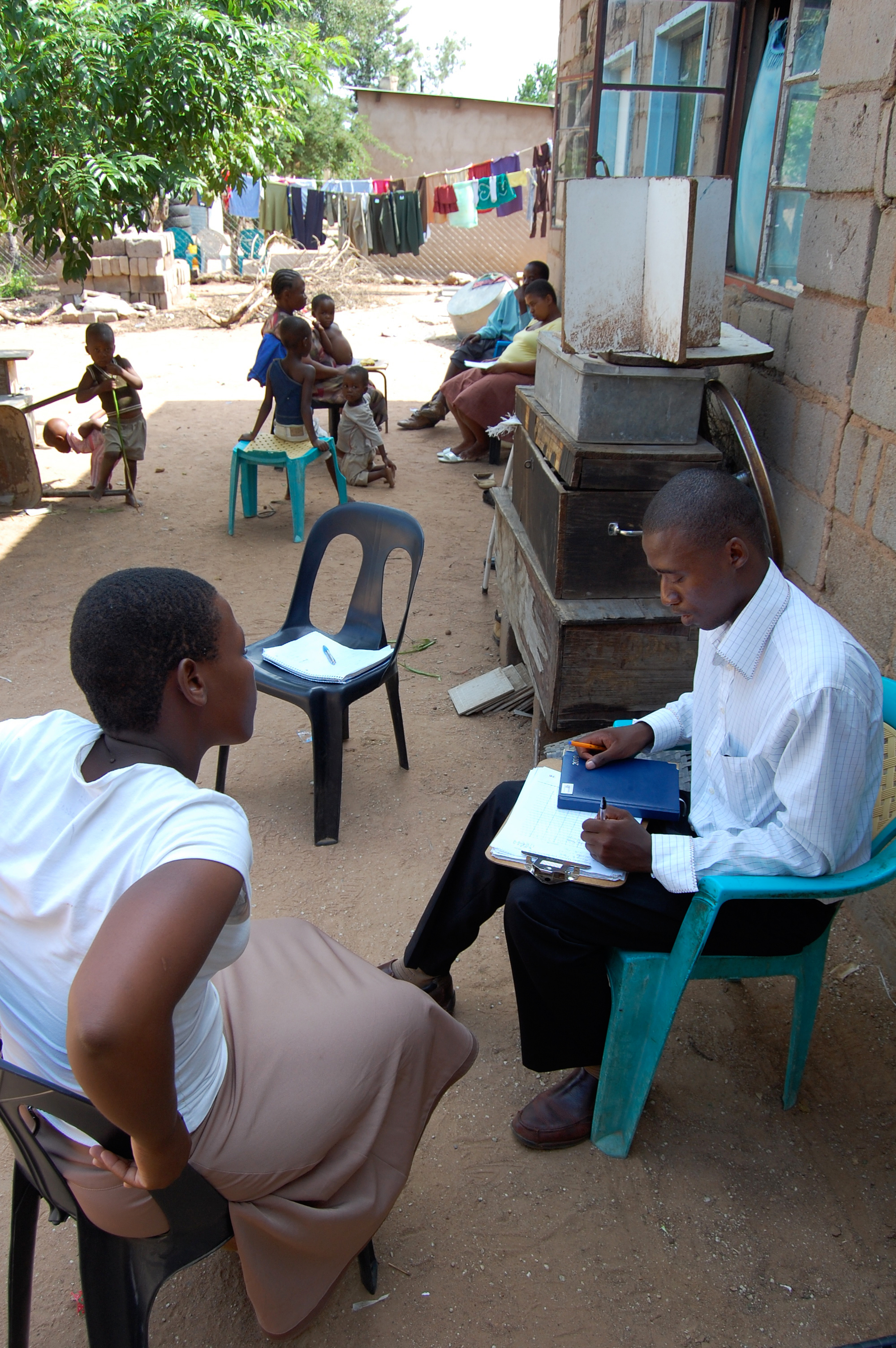 Male Botswanan Doctor working with young woman patient outside, with children waiting in the background