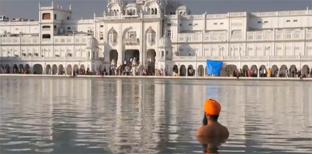 South Asian Man in Water Staring at Golden Temple in Amritsar