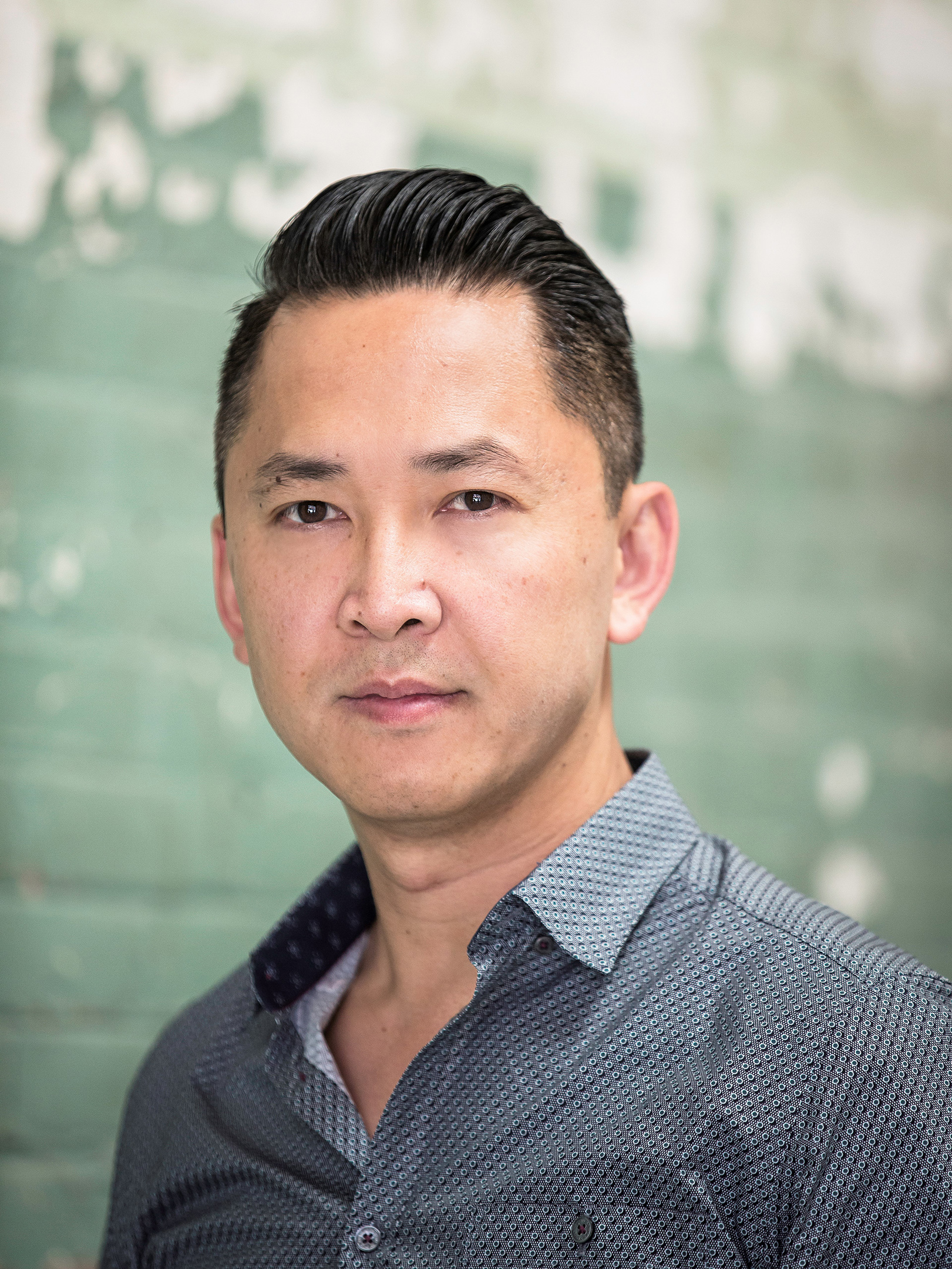 Author Viet Thanh Nguyen in blue white shirt, seated in front of in front of a light green painted wall