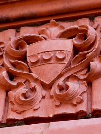 tight crop of a terracotta penn shield on building facade