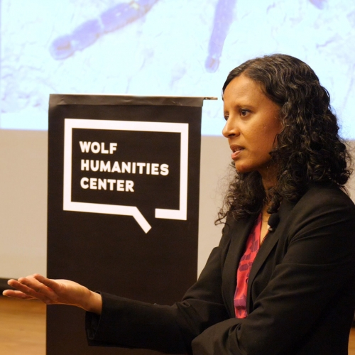 Lecturer Sanchita Balachandran in front of Wolf Humanities Center banner