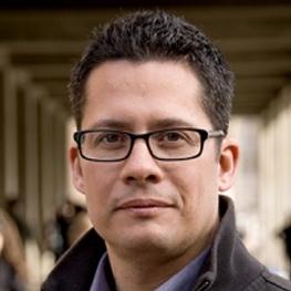 Roberto Gonzales standing in front of a school hallway