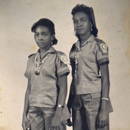 Two Cuban women in military outfits posing side by side in a vintage photograph