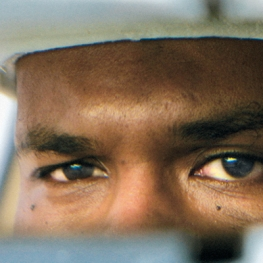 Close up of a person's face in a rear view mirror from Film poster of The Oath (dir. Laura Poitras, 2010, 96 min.)