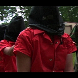 Film still from Operation Atropos. Women in orange jump suits with black hoods over their heads.