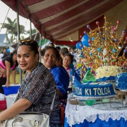 Film still from For My Father's Kingdom. Women in Tonga sit at a table alongside a festive cake.