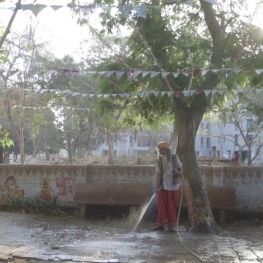 Film still from Welcome Valentine. A Hindu priest in India uses a hose to spray down a court yard.