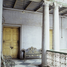 Inside Expensive Older Building with Columns, gold benches, and high ceilings