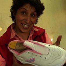 Film still from Vivir La Chicha. Woman holding a sneaker.
