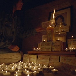 Film still from Ghosts and Numbers. Woman lighting a candle next to a grave.