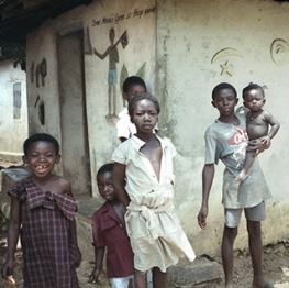 Young Ghanain Children in Front of Building with Mural