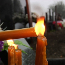 Film still from Letter for Dad. Candle being lit in foreground of graveyard